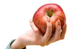 Main femelle jugeant une pomme d'isolement sur le blanc Photographie stock libre de droits