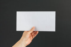 Main femelle livrant une enveloppe blanche sur le fond noir Photos stock