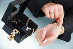 Main femelle mettant vers le haut du bracelet Photo libre de droits
