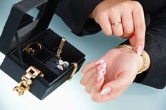 Main femelle mettant vers le haut du bracelet Photo stock