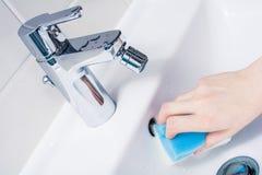 Main femelle nettoyant le débordement de bassin avec une éponge dans la salle de bains photographie stock