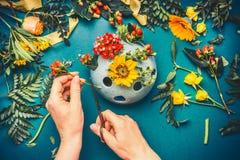 Main femelle prenant des dispositions de fleurs d'automne au fond bleu d'espace de travail de fleuriste Images libres de droits