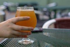 Main femelle prenant sa bière d'une table photos stock