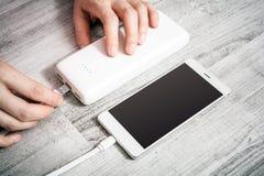 Main femelle reliant Smartphone à de basses batteries avec Powerbank pour recharger l'énergie, vue courbe Images libres de droits