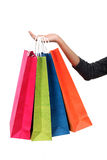 Main femelle retenant les sacs à provisions colorés image stock