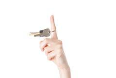Main femelle spining une clé d'isolement sur le fond blanc Photos libres de droits