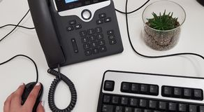 Main femelle sur la souris noire d'ordinateur près du téléphone de bureau image libre de droits