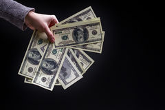 Main femelle tenant cent billets d'un dollar sur le fond noir C Photo libre de droits
