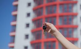 Main femelle tenant des clés sur le fond de la nouvelle maison Concept 6 d'immeubles Clés au nouvel appartement Maison ou locatio Photographie stock libre de droits