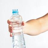 Main femelle tenant la bouteille d'eau douce Photo libre de droits