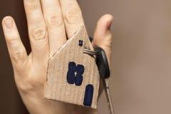 Main femelle tenant la clé de maison, vrai agent immobilier Photo stock