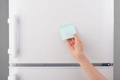 Main femelle tenant la note de papier collante bleue vide sur le réfrigérateur Photographie stock