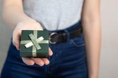 Main femelle tenant la petite case avec un cadeau L'espace vide image libre de droits
