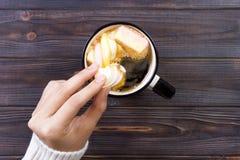 Main femelle tenant la tasse de cacao ou de chocolat chaud avec la guimauve sur la table en bois d'en haut Photographie stock libre de droits