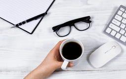 Main femelle tenant la tasse de café sur le bureau blanc organisé Image stock