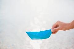 Main femelle tenant le bateau de papier Photographie stock