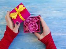 Main femelle tenant le boîte-cadeau avec la félicitation romantique d'anniversaire d'arc, fleur rose sur le fond en bois bleu image libre de droits