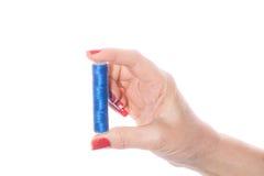 Main femelle tenant le fil de couture bleu sur un blanc Images stock