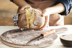 Main femelle tenant le pain fraîchement cuit au four chaud image stock