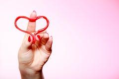 Main femelle tenant le symbole rouge d'amour de coeur Rose rouge Image stock