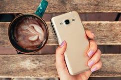 Main femelle tenant le téléphone intelligent au café, avec le cappuccino sur le tabl photographie stock libre de droits