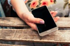 Main femelle tenant le téléphone intelligent avec l'écran vide, à la table Images libres de droits