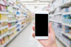 Main femelle tenant le téléphone portable avec le fond de supermarché Photos stock
