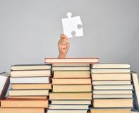 main femelle tenant un grand puzzle blanc et une pile de livres images libres de droits