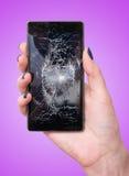 Main femelle tenant un téléphone intelligent mobile avec l'écran cassé Images stock