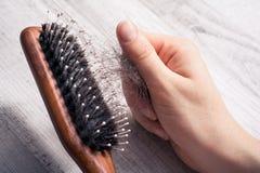 Main femelle tirant le groupe de cheveux hors de la brosse - concept de perte des cheveux d'alopécie Photographie stock