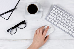 Main femelle utilisant la souris d'ordinateur sur le bureau blanc organisé Photos stock