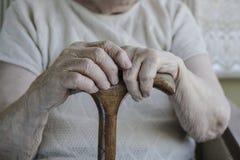 Main froissée d'une femme supérieure sur la canne Photographie stock libre de droits