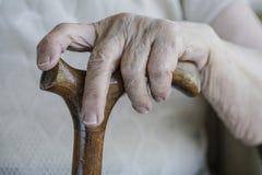 Main froissée d'une femme supérieure sur la canne Photos libres de droits