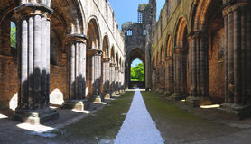Main gallery of Kirkstall Abbey ruins, Leeds, UK. Panoramic view of the main gallery perspective of Kirkstall Abbey ruins, taken in birght summer sunlight, Leeds Royalty Free Stock Images