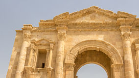 Main gate Hadrian`s Arch in Jerash in Jordan. In front of a blue sky Stock Image