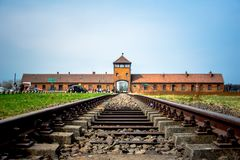 Main gate to nazi concentration camp of Auschwitz Birkenau with train rail. Poland on April 14, 2018. Here were exterminated 1.5 million people at the second Royalty Free Stock Photos
