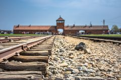 Main gate to nazi concentration camp of Auschwitz Birkenau. With train rail, Poland Stock Image