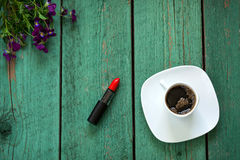 The main girly things. Morning beauty routine. Red Lipstick and cup of coffee on wooden table decorated violet flowers and berries Royalty Free Stock Image