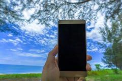 Main haute étroite de jeune femme tenant une moquerie noire moderne de smartphone dans la position horizontale avec l'écran vide  images stock
