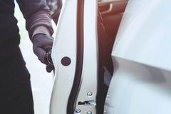 Main haute étroite tirant la poignée d'un voleur de voiture portant les vêtements noirs et du gant volant la poignée de porte de  images stock