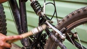 Main humaine époussetant la bicyclette professionnelle avec la brosse clips vidéos