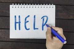 Main humaine avec le texte d'écriture de marqueur sur le bloc-notes : Aide photos stock