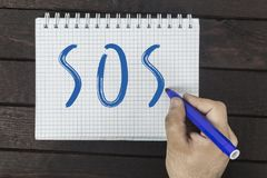 Main humaine avec le texte d'écriture de marqueur sur le bloc-notes : SOS image stock