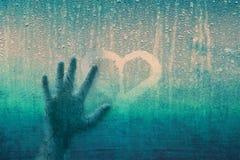 Main humaine criquée sur la fenêtre avec le signe de coeur Image stock