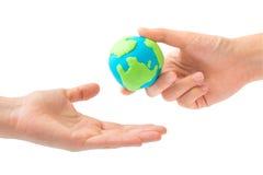 Main humaine envoyant la terre dans une autre main Image libre de droits