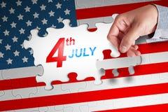 Main humaine finissant un puzzle de drapeau américain avec le quatrième 4ème de J Image stock