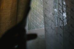 Main humaine glissant un rideau au côté images libres de droits