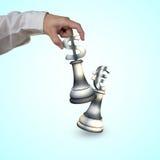 Main humaine jouant des pièces d'échecs de symbole monétaire d'argent Photographie stock libre de droits