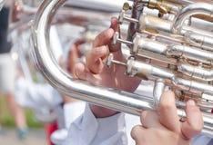 Main humaine jouant la bugle image stock