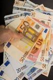 Main humaine jugeant des billets de banque d'argent-euro d'isolement sur un fond gris-foncé Photographie stock